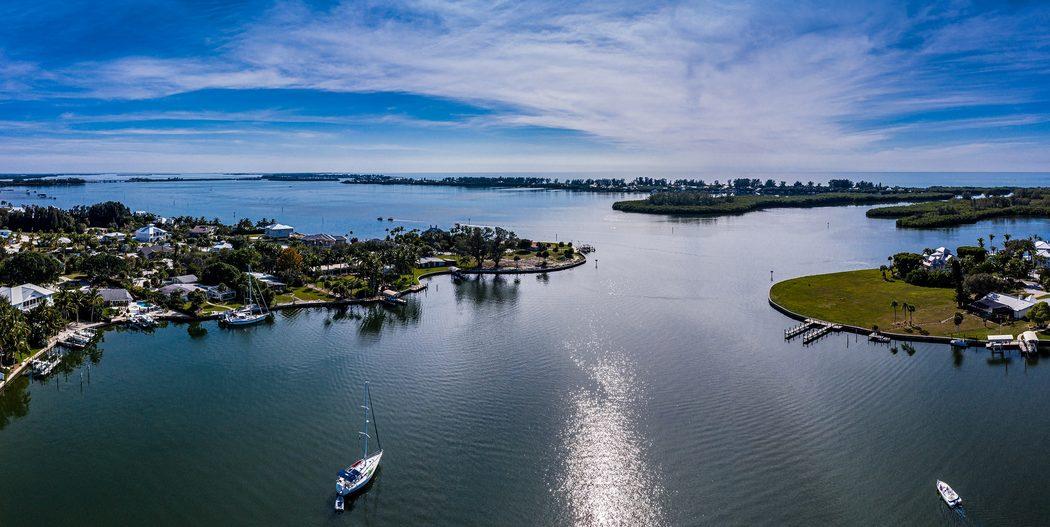 Bucht in Charlotte County, in der ein Segelboot und eine Motoryacht liegen, und im Hintergrund der Coastal Waterway zu sehen ist.