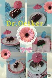 Dr. Oetker Kleine Rührkuchen, Sorte Schokolade, schön dekoriert mit Zuckerperlen auf einem bunten Teller angerichtet.