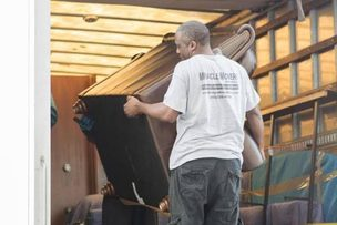 Miracle mover loading furniture onto moving truck in Greensboro NC