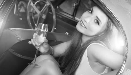 Escort Lady in Limousine mit Sektglas