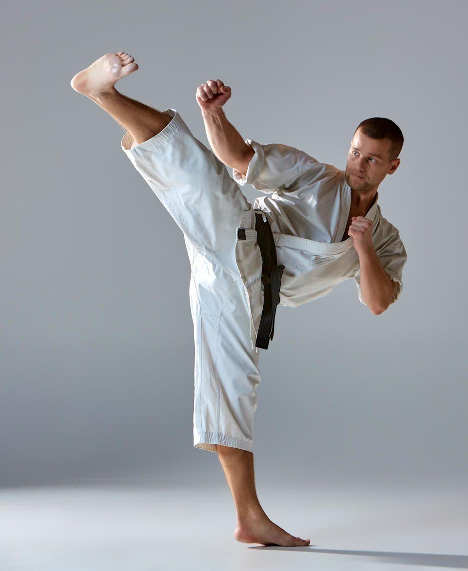 Kampfkünstler mit schwarzem Gürtel während eines hohen Kicks.